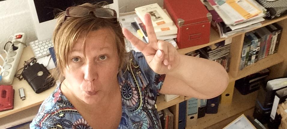 Frau am Schreibtisch macht ein Peacezeichen