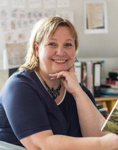 Autorin sitzt am Schreibtisch