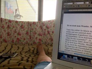 Ein Laptap ein Bein in einem Bett